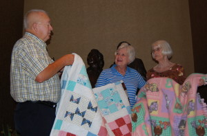 Glen , Andrea and Edna with Edna's quilt to be auctioned at MTSU game and a blanket for children staying in the Fisher House
